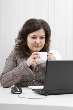 The young business woman with coffee mug at office Stock Photo - 6594484