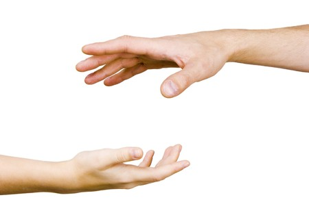 childs hand reaches for the male hand on a white background  photo