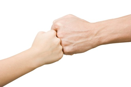 Fist of the child rests on the fist man on an isolated white background Stock Photo - 7747366