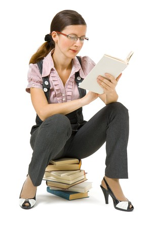 young girl with glasses sitting on a pile of books and reading