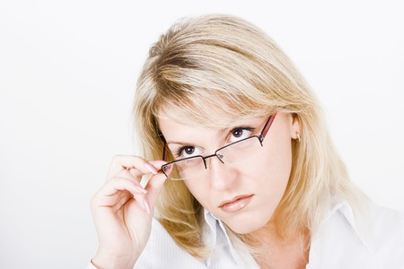 Strict blonde girl with glasses on a light background  photo