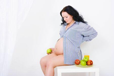 pregnant girl is sitting on a small table in the studio  photo