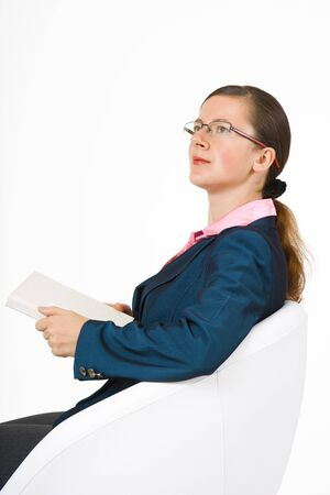 Slim girl in glasses with a book sitting in white chair  photo