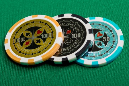 three poker chips on a green background fabric photo