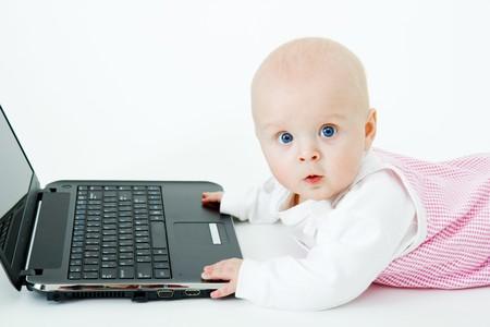 スタジオで白い背景の上のノート パソコンと赤ちゃん 写真素材
