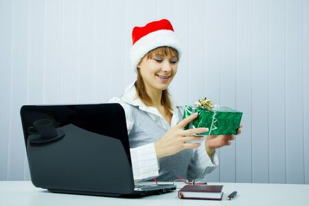 happy business woman in Santa hat with a gift at the office Stock Photo - 8370864
