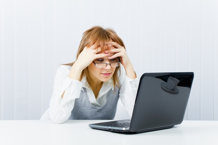 weary worker in the office with a laptop. Girl with glasses  photo