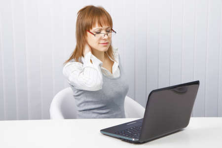 tired worker in the office. Disheveled girl with laptop. neck pain Stock Photo - 8736070