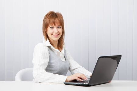 Attractive smiling happy girl with a laptop in the office Stock Photo - 8949760