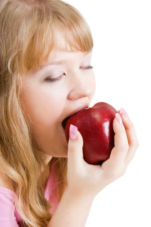 blonde girl bites the big red apple on a white background  photo