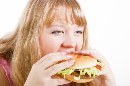 overeat: The young hungry woman bites the big hamburger Stock Photo