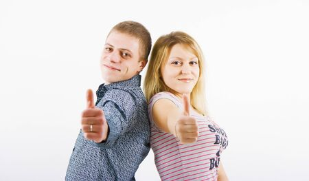 young happy couple with a thumbs up standing back to back  photo