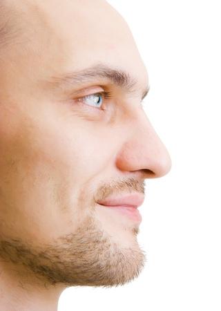 白い背景上のプロファイルで幸せそうな顔ひげを剃っていない若い男