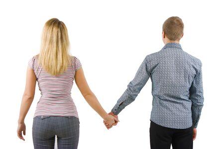 カメラに戻って手を繋いでいる若いカップル。白い背景で隔離
