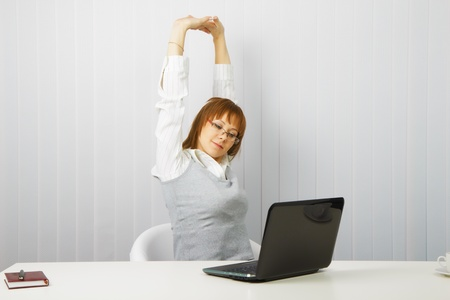 tired girl with a laptop stretches in the workplace photo
