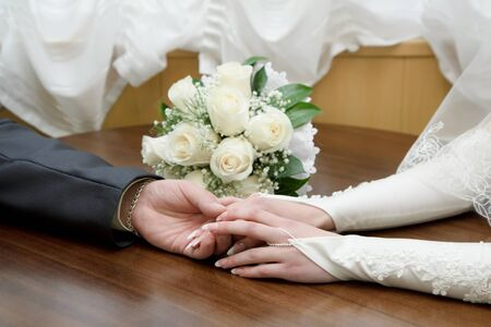 hands of the bride and groom on the background of a wedding bouquet