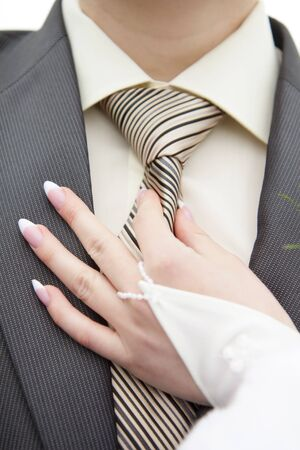 beautiful bride holds the hand of the grooms tie  Stock Photo