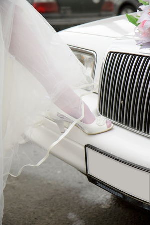 leg of the bride in white shoes on the bumper limousine photo
