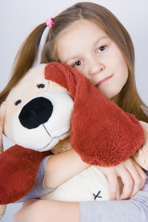 sad girl hugging a toy dog. Portrait of a close-up  photo