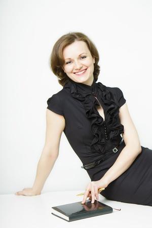 テーブルの上に座ってビジネス黒ドレスの魅力的な若い女性の笑みを浮かべてください。