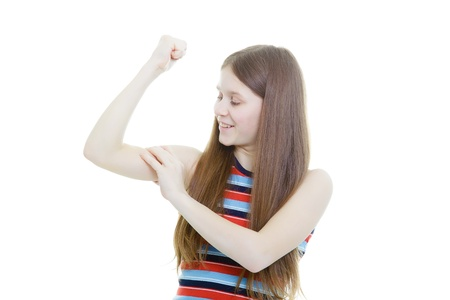 smiling teenage girl measuring her biceps on a white background  photo