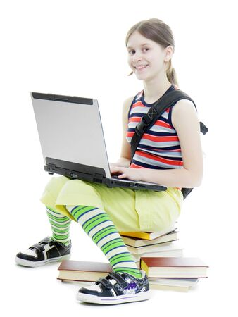 Teen girl smiling in a summer dress with a laptop sitting on the books. White background