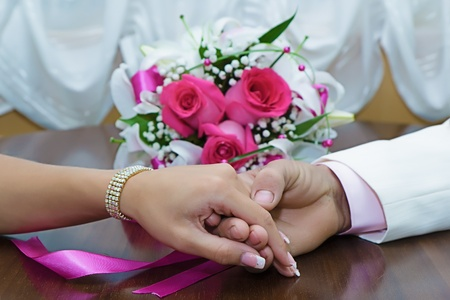 the hands of the newlyweds and bridal bouquet on the table Stock Photo