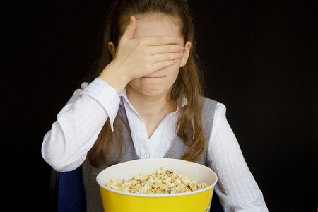 blind people: girl in a movie theater closes her eyes Stock Photo