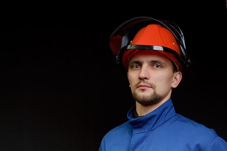The worker in overalls and a helmet on a black background  photo