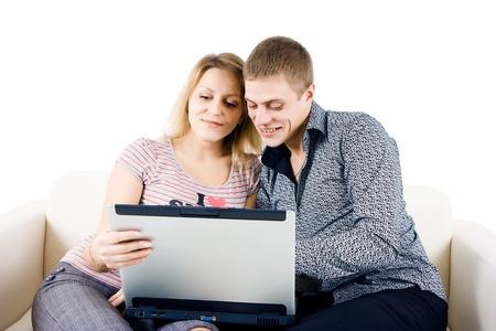 Glückliche junge Paar mit einem Laptop auf der Couch sitzen