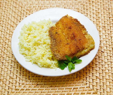 fried tilapia with rice garnish on a white plate photo