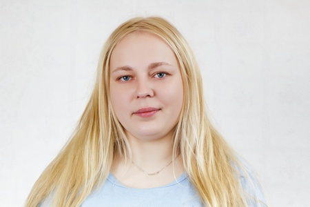 chubby blonde girl in a blue shirt on a white background. portrait Stock Photo