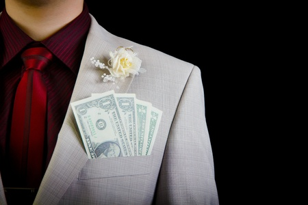 dollars in the pocket of the groom wedding dress on a black background photo