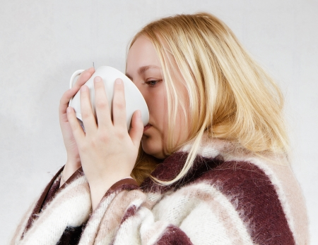 girl with a cup wrapped in a blanket. white background photo