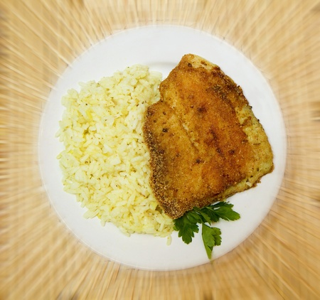fried breaded tilapia served with rice and herbs photo