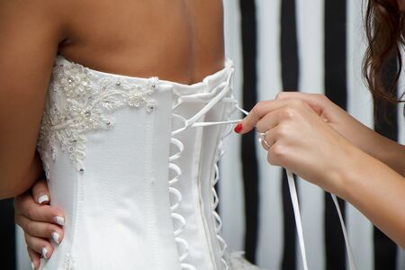 bridesmaid helps the bride to tie the corset photo