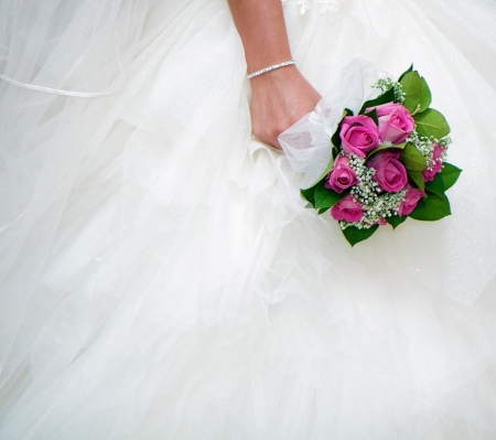 wedding accessories: bridal bouquet on a background of white wedding dresses