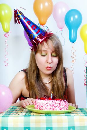 Birthday. An attractive young girl blows out the candle on the cake photo