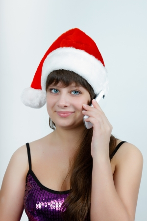 attractive girl in a Christmas hat talking on a cell phone Stock Photo - 14718770