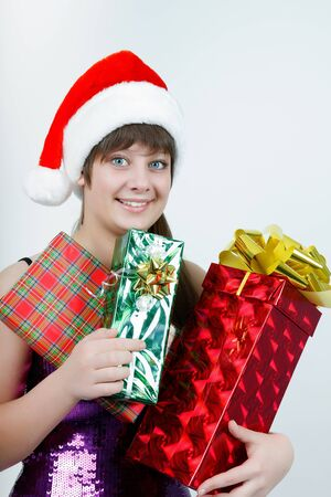 attractive girl in a Christmas hat with a bunch of gift boxes Stock Photo - 14718772
