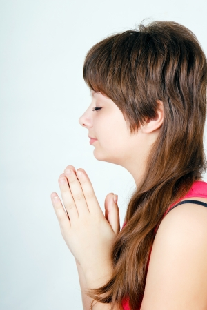 Attractive teen girl praying with folded hands photo