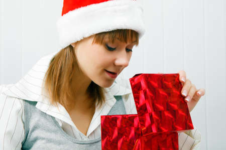 Attractive girl opens a Christmas present. office scene photo