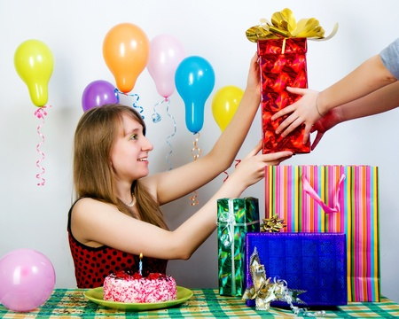accepts: Birthday. The girl happily accepts gifts from friends