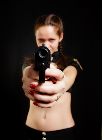 sexy girl with gun on black background photo