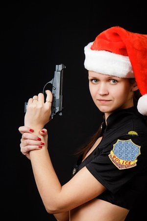 sexy girl cop in Christmas fancy dress with a gun on a black background photo