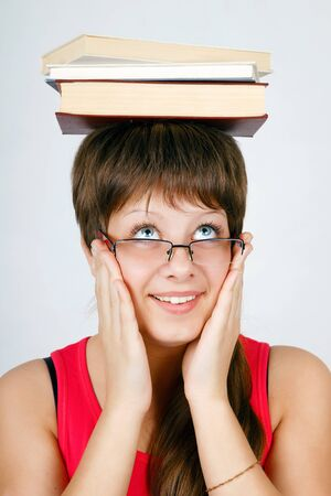 girl in glasses with the books on head on an isolated white background photo