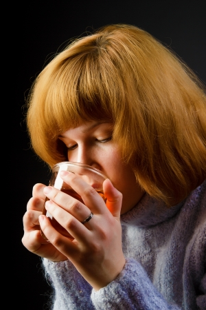 girl in a sweater on a black background drinking tea from a transparent cup. portrait photo