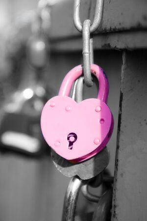 pink wedding lock hanging on the bridge photo