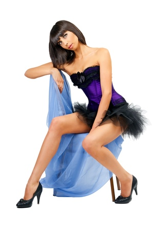 Sexy tanned girl in a mini skirt posing on a chair photo