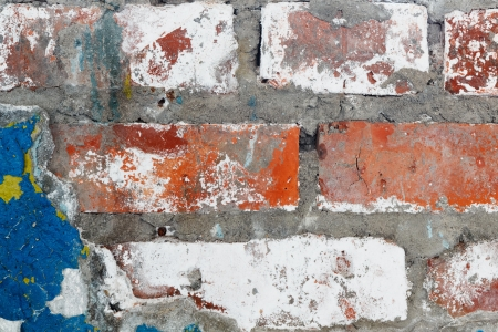 Old plaster with remnants of paint on a brick wall photo